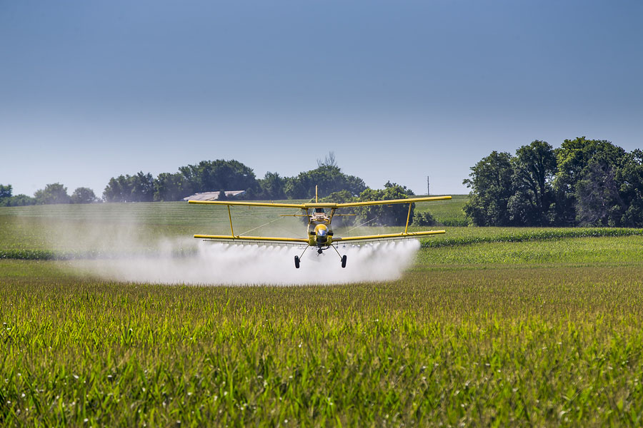 bigstock-A-crop-duster-applies-chemical-97488557